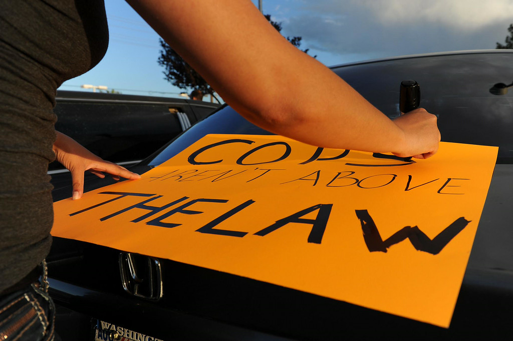 """. Jessica Jones, 25, of Fontana, creates a sign stating \""""cops aren\'t above the law\"""" during a protest against police brutality in honor of Dante Parker on Wednesday, August 20, 2014 in Victorville, Ca.  The protest was organized by CopsWatch IE and drew about thirty people. (Photo by Micah Escamilla/The Sun)"""