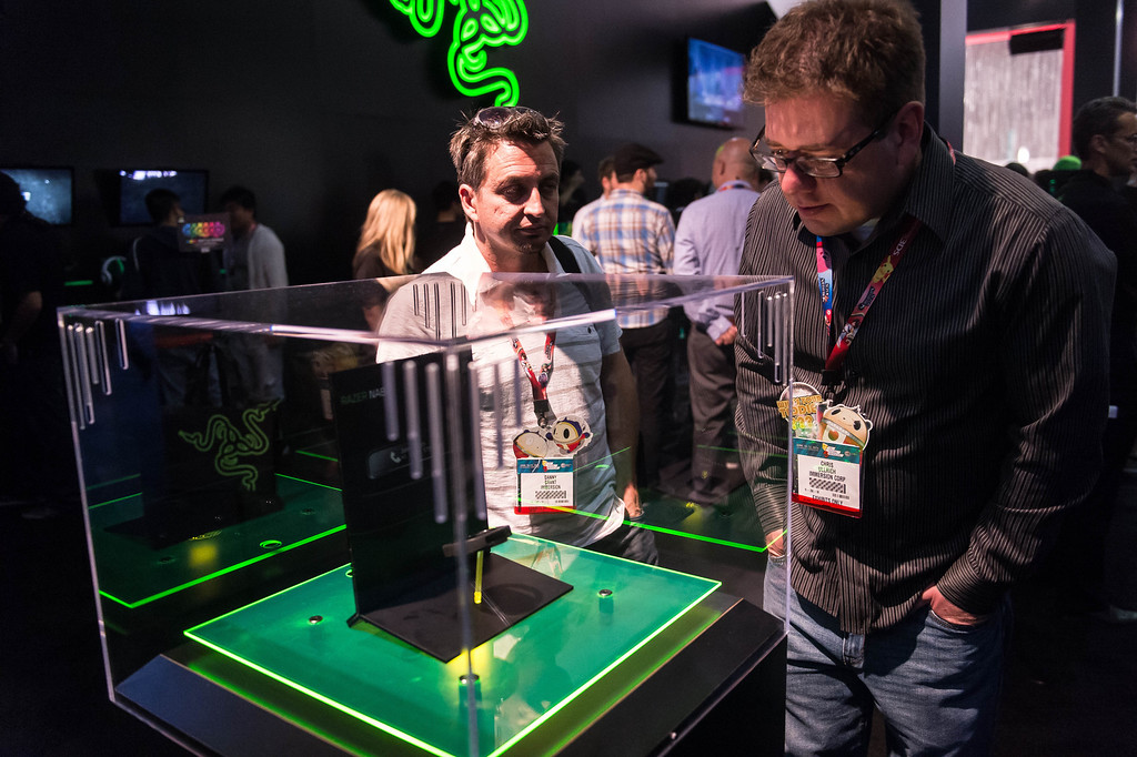 . Attendees look at the Razer smartband in a display case at Electronic Entertainment Expo in Los Angeles on Tuesday, June 10, 2014. (Photo by Watchara Phomicinda)