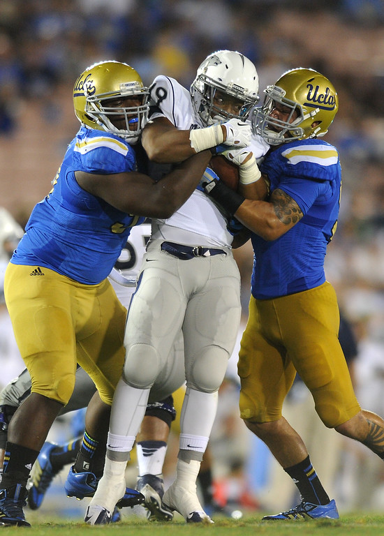 . UCLA\'s Kenneth Clark, left, and Myles Jack sandwich Nevada\'s Nate McLaurin in the fourth quarter, Saturday, August 31, 2013, at the Rose Bowl. (Michael Owen Baker/L.A. Daily News)