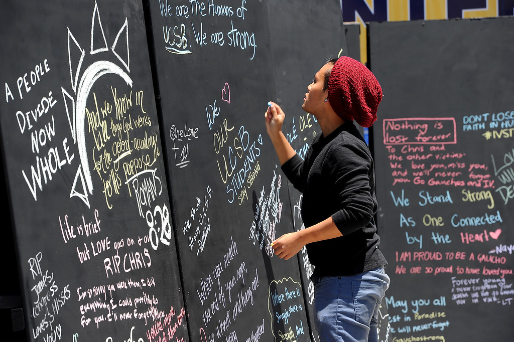 . UCSB student Alex Nguyen writes a message on a remembrance wall in Isla Vista, Tuesday, May 27, 2014, for the victims of Friday night\'s murder spree. (Photo by Michael Owen Baker/Los Angeles Daily News)