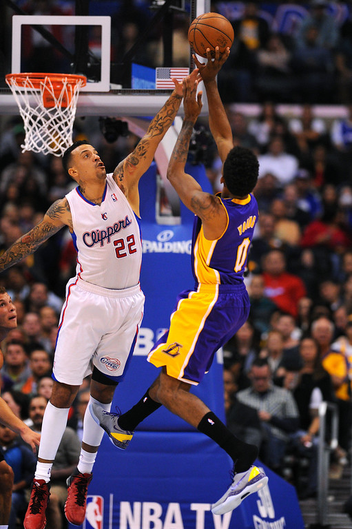 . The Lakers\' Nick Young jumps out of his left shoe as he shoots against the Clippers Matt Barnes, Friday, January 10, 2014, at Staples Center. (Photo by Michael Owen Baker/L.A. Daily News)