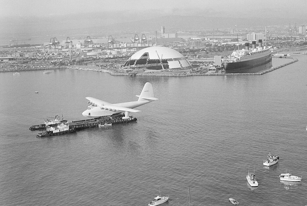""". \""""Spruce Goose,\"""" the flying boat belonging to the late millionaire Howard Hughes, is gingerly edged across the Los Angeles harbor near Long Beach, Calif., by two tugs pushing a barge on which the huge plane is mounted, during the move, Feb. 12, 1982.  The plane will be put on public display next to another popular attraction, the former luxury liner Queen Mary, right, background.  (AP Photo/Wally Fong)"""