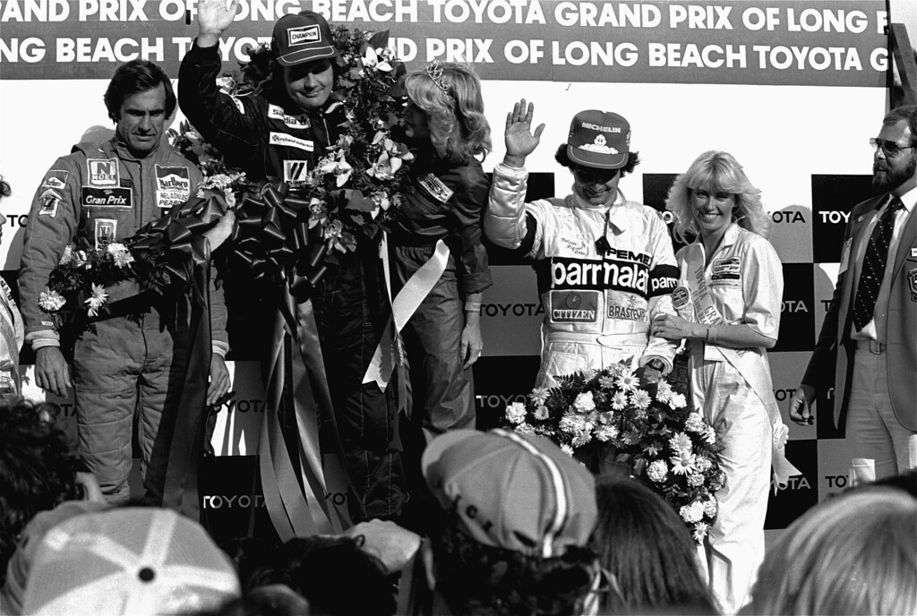 . Argentine race car driver Carlos Reutemann of the Williams racing team, left, who came in second in the Long Beach, Calif. Grand Prix Sunday, March 15, 1981 stands with winner Alan Jones of Australia, accompanied by Queen Karen Reynolds in the winner\'s circle. Third place finisher Nelson Piquet is at right. (AP Photo)
