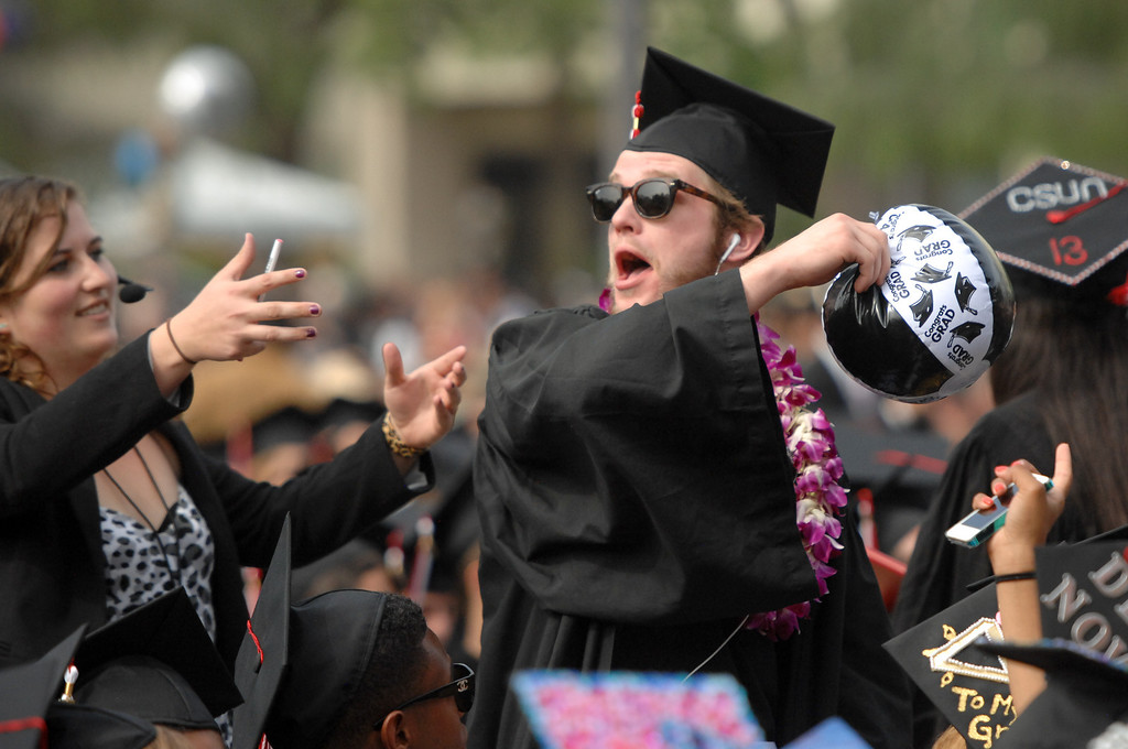 . A graduate tosses an inflatable ball as an usher moves in for the take away at the CSUN the commencement ceremony, Tuesday, May 21, 2013. (Michael Owen Baker/L.A. Daily News)