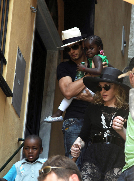 ". Photo taken Monday Aug. 17, 2009 made available Tuesday Aug. 18, 2009 of U.S. singer Madonna, at right, holding hands with her adopted child from Malawi David Banda, bottom left, followed by Brazilian model Jesus Luz, top  left, holding her other adopted child Chifundo ""Mercy\"" James, in Italy\'s northwestern riviera town of Portofino. Reports said Tuesday Madonna is in the seaside resort town to spend some time with Italian designers Dolce and Gabbana and other friends. After adopting David Banda in 2008, Malawi\'s highest court had granted the adoption of Chifundo \""Mercy\"" James June 12, 2009 overturning an April lower court ruling that Madonna had not spent enough time in Malawi to be given a child. Madonna\'s Raising Malawi, a charity founded in 2006, helps feed, educate and provide medical care for some of Malawi\'s orphans.  (AP Photo)"