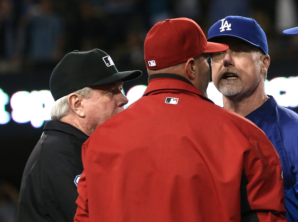 . LOS ANGELES, CA - JUNE 11:  Batting coach Mark McGwire (R) of the Los Angeles Dodgers has words with manager Kirk Gibson of the Arizona Diamondbacks as first base umpire Brian Gorman intervenes during a bench clearing brawl in the seventh inning at Dodger Stadium on June 11, 2013 in Los Angeles,  (Photo by Stephen Dunn/Getty Images)