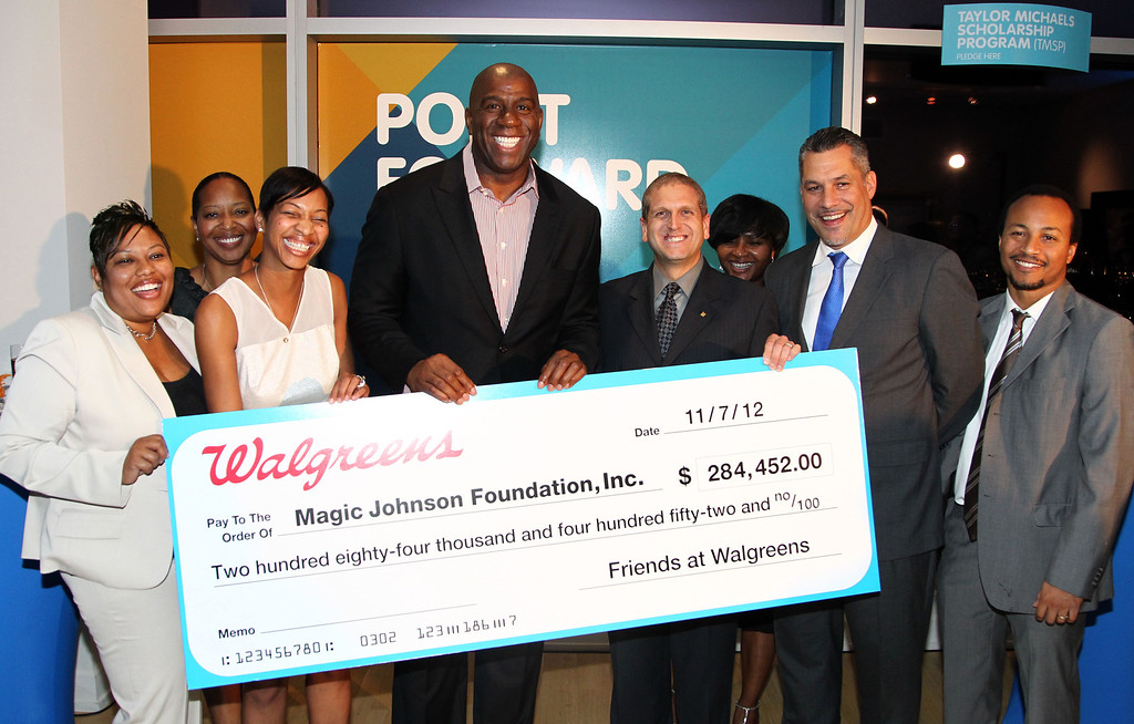 """. Magic Johnson, center, and the team from the Magic Johnson Foundation accept a check from Walgreens at \""""A Toast To Possibilities\"""" celebrating the Magic Johnson Foundation\'s Point Forward Day at The Ritz Carlton Residences at L.A. Live on Wednesday, Nov. 7, 2012, in Los Angeles.  (Photo by Matt Sayles/Invision for AEG Worldwide/AP)"""