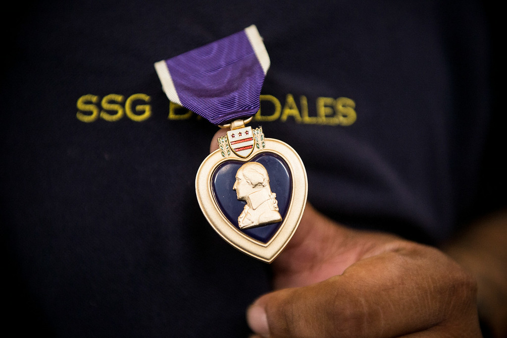 . Sgt. Luis Bardales, a resident of Irwindale who works for the city of South Pasadena, shows his Purple Heart at the Army National Guard in Azusa Saturday, July 12, 2014 after a ceremony in his honor. Bardales was wounded by a roadside IED in Baghdad, Iraq and saved gunner Gabriel Herrera by pulling him out of their Humvee before another IED explosion. (Photo by Sarah Reingewirtz/Pasadena Star-News)