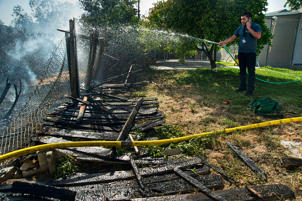 . Brandon Perla, 25, sprays water on the burned fence in his backyard during a brushfire in the 6000 block of Portsmouth Street in Chino on Wednesday, May 1, 2013. The wind driven fire burned several fences and power poles along the soundwall north of the 60 Freeway between Magnolia Ave and Oak Ave.  (SGVN/Staff photo by Watchara Phomicinda)