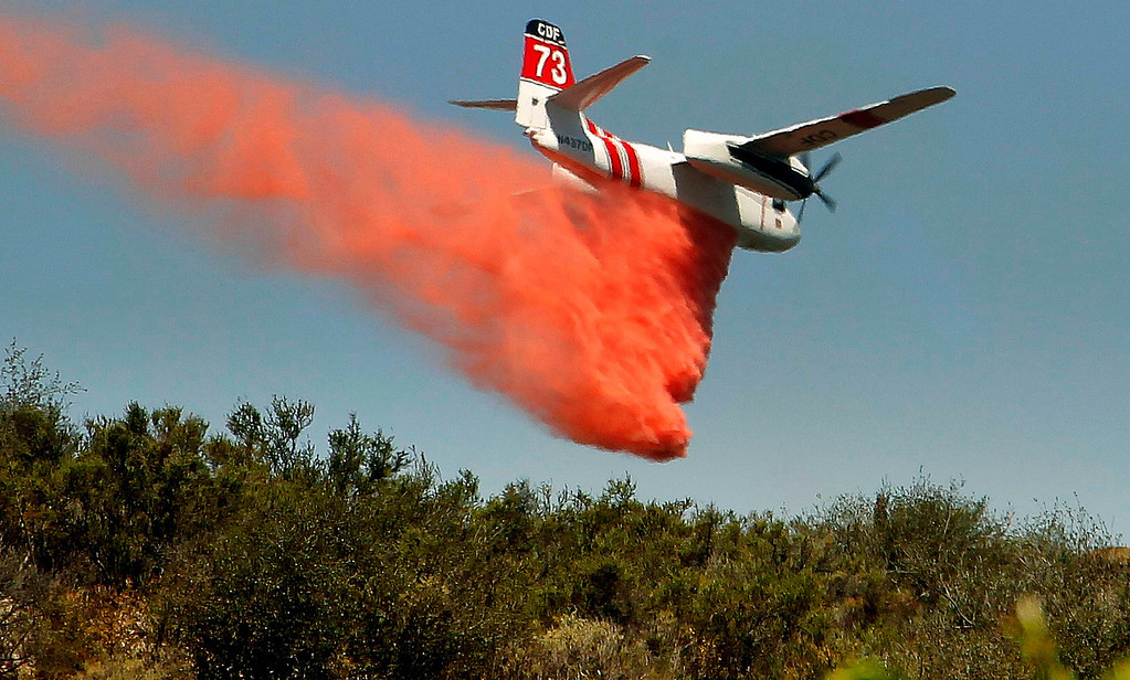 . A firefighting aircraft drops fire retardant along a hill side near Thousand Oaks, Calif. on Thursday, May 2, 2013. A 2,000-acre blaze that began in the Camarillo area along U.S. 101 in Ventura County was uncontained. It prompted the evacuation of a Thousand Oaks neighborhood and the campus of California State University, Channel Islands. At least a half-dozen RVs burned in a parking area enclosed by brushy hills. Embers scattered along ridges and into neighborhoods abutting the brush lands and smoke streamed for miles. More than 200 firefighters were aided by water- and fire retardant-dropping aircraft. (AP Photo/Nick Ut)