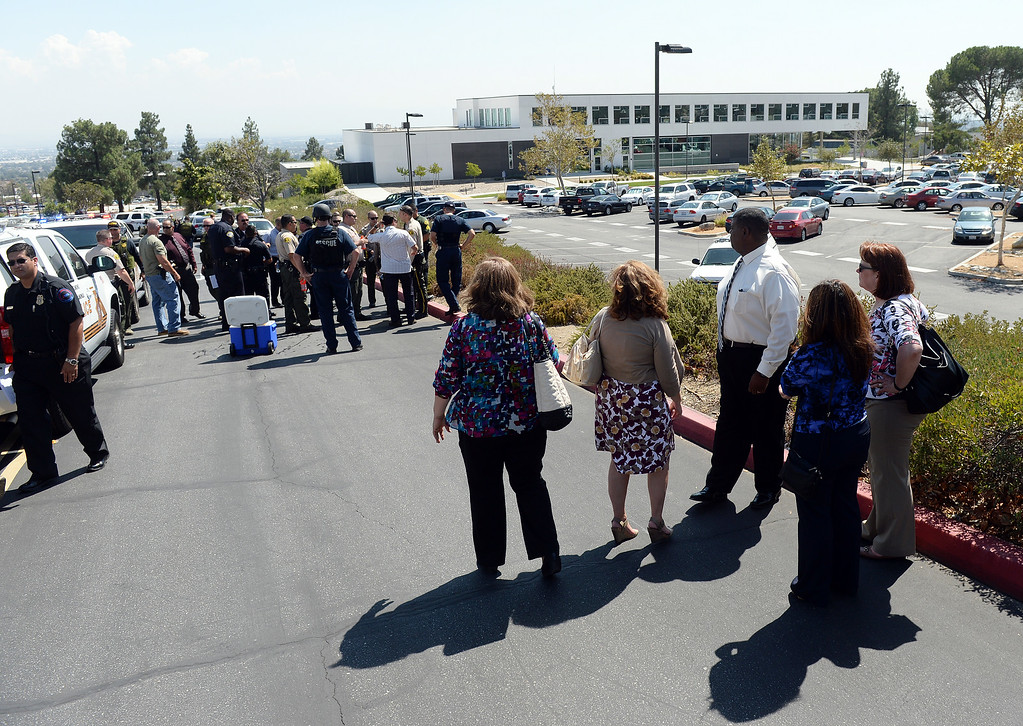 . Chaffey College employees watch as sheriff deputies and campus police work at the command post on the north side of the campus as they search for a possible threat on campus Thursday. The Chaffey College campus in Rancho Cucamonga was lockdown by campus police at approximately 1:15 p.m Thursday August 21, 2014 after a report was made about a maie with anti-goverment patches on his vest, wearing black combat boots, black pants and a black backpack. The threat was never confirmed and no one was taken into custody. The campus was under lockdown for over an hour before it was lifted. Classes have been cancelled for the rest of the day.  (Will Lester/Inland Valley Daily Bulletin)