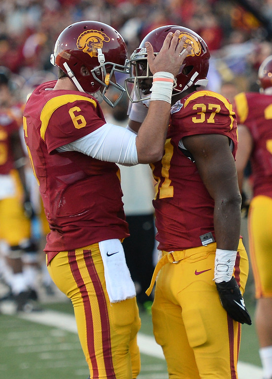 . LAS VEGAS, NV - DECEMBER 21:  Quarterback Cody Kessler #6 of the USC Trojans congratulates teammate Javorius Allen #37 after they scored a touchdown against the Fresno State Bulldogs during the Royal Purple Las Vegas Bowl at Sam Boyd Stadium on December 21, 2013 in Las Vegas, Nevada. USC won 45-20.  (Photo by Ethan Miller/Getty Images)