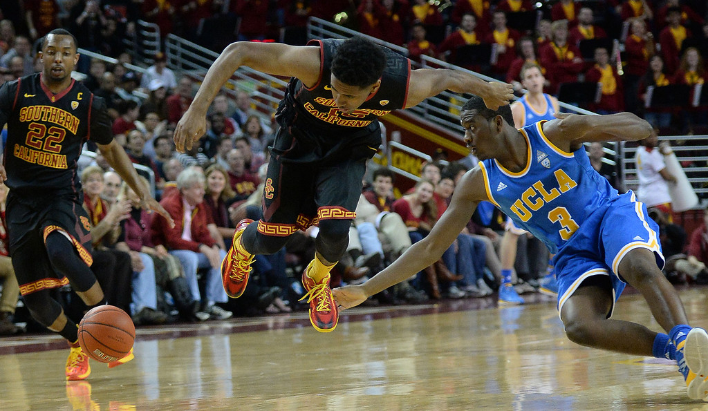 . UCLA\'s Jordan Adams (3) scrambles for the loose ball with Southern California\'s Brendyn Taylor  (15) in the first half of a PAC-12 NCAA basketball game at Galen Center in Los Angeles, Calif., on Saturday, Feb. 8, 2014. (Keith Birmingham Pasadena Star-News)