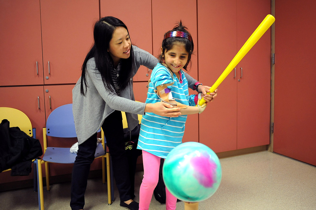. Occupational therapist Vivian Yip teaches Shah Bibi how to swing a bat at Shriners Hospital for Children in Los Angeles, CA April 2, 2014.  Bibi lost most of her right arm and the use of an eye after picking up a hand grenade.  She was brought to Southern California for medical treatment in December by the Children of War Foundation and is set to return to her remote Afghani village next week.(Andy Holzman/Los Angeles Daily News)