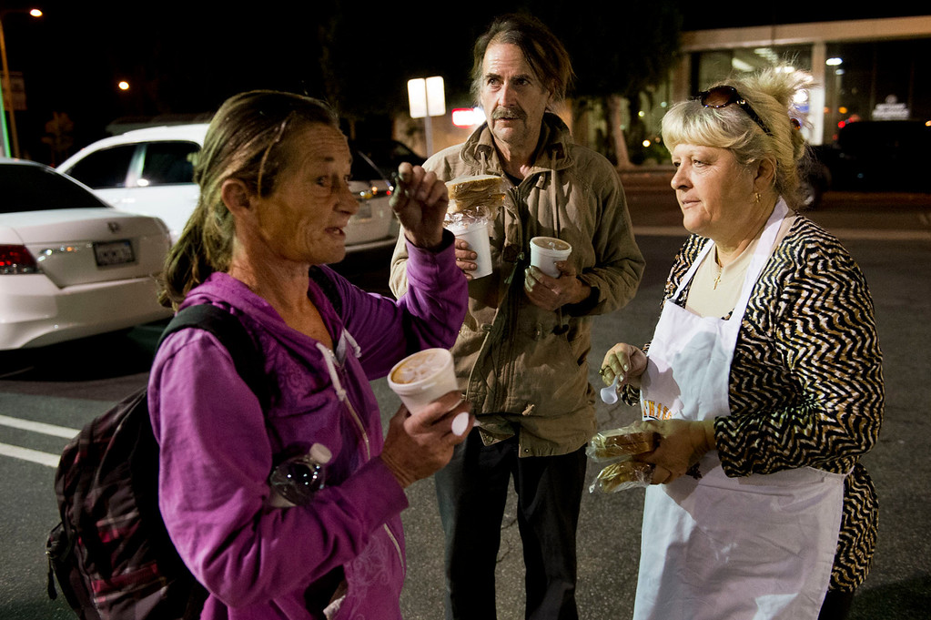 . Nicolette Wingert, right, greets homeless denizens, Deanne, left, and Paul, after the two sandwiches and hot soup in a parking lot in Glendora on Wednesday night, Nov. 27, 2013. Nicolette Wingert has been feeding the homeless six days a week for the past seven years with Nurses4Christ, a nonprofit organization she founded in 2006. She and Phillip Stern of Glendora have been going every day since 2008, feeding homeless people sandwiches and hot food; giving them bottles of water, clothes and blankets. (Photo by Watchara Phomicinda/San Gabriel Valley Tribune)
