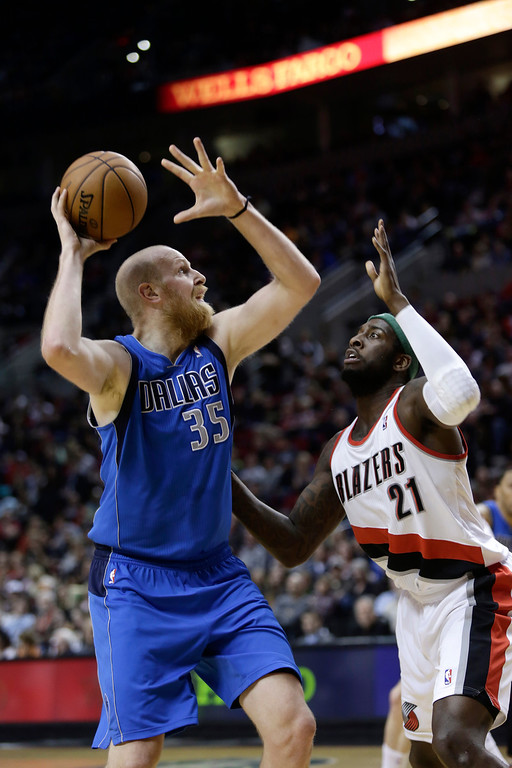 . Dallas Mavericks center Chris Kaman, left, looks to shoot over Portland Trail Blazers center J.J. Hickson during the second half of an NBA basketball game in Portland, Ore., Sunday, April 7, 2013. (AP Photo/Don Ryan)