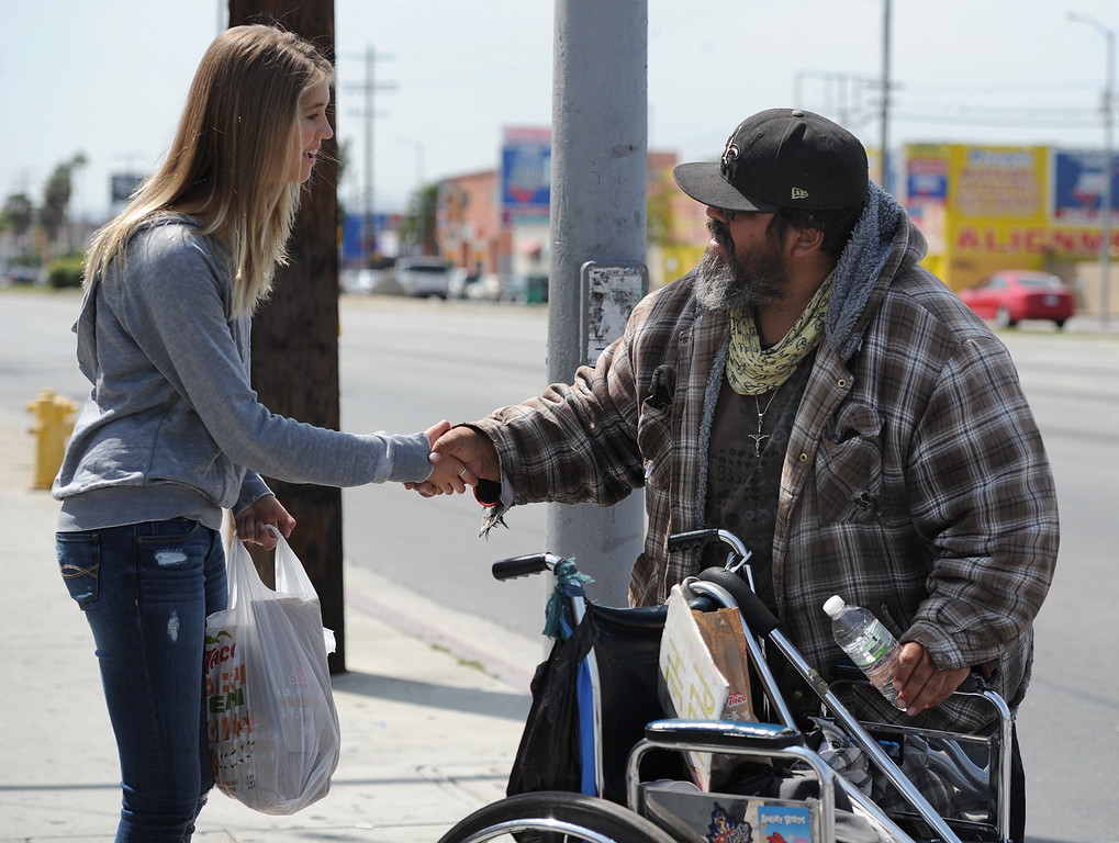 . Lexi Di Benedetto shakes hands with homeless man Frank Pacheco after giving him a bag of food, and some water. Our Lady of Peace Parish and School hosted its first Love It Forward Event. Members of the parish, and community, went out into the streets to spread love with simple, random acts of kindness. North Hills, CA. March 29, 2014 (Photo by John McCoy / Los Angeles Daily News)