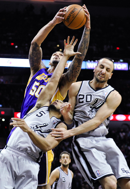 . Los Angeles Lakers center Robert Sacre grabs a rebound over San Antonio Spurs guards Cory Joseph, left, and Manu Ginobili of Argentina during the second half of an NBA basketball game  Friday, March 14, 2014, in San Antonio. (AP Photo/Bahram Mark Sobhani)