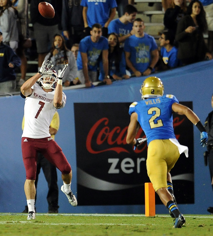 . New Mexico State wide receiver Adam Shapiro (7) catches a pass for a touchdown over UCLA defensive back Priest Willis (2) during the second half of their college football game in the Rose Bowl in Pasadena, Calif., on Saturday, Sept. 21, 2013.   (Keith Birmingham Pasadena Star-News)