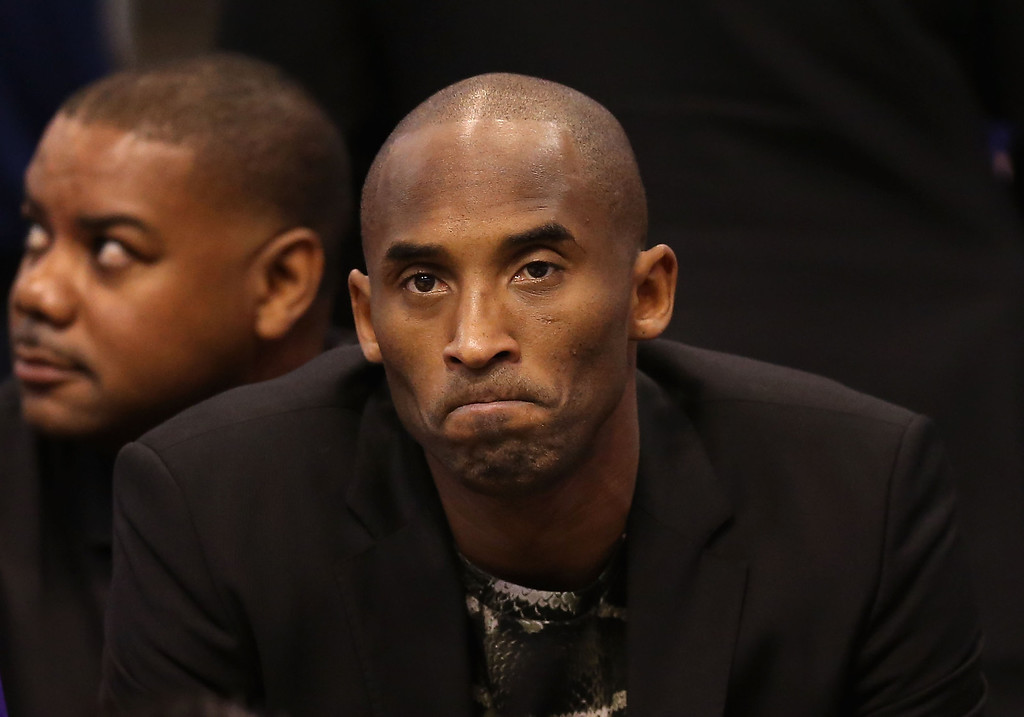 . Kobe Bryant #24 of the Los Angeles Lakers watches from the bench during the NBA game against the Phoenix Suns at US Airways Center on January 15, 2014 in Phoenix, Arizona.    (Photo by Christian Petersen/Getty Images)