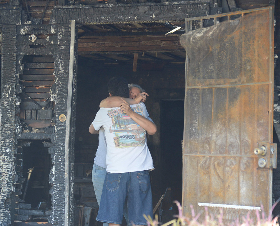 . Local neighbor and close friend Michelle Lesser hugs a neighbor after the lost of her friend was killed in a house fire Saturday night in Burbank. The fire was reported at about 9:20 p.m. Saturday at 910 North Evergreen St.  Flames were showing when firefighters arrived with three people were in the house when the fire broke out. One person died in the fire, but two people got out and were transported to a hospital with non-life threatening injuries. Oct 20, 2013. Burbank CA. Photos by Gene Blevins/LA Daily News