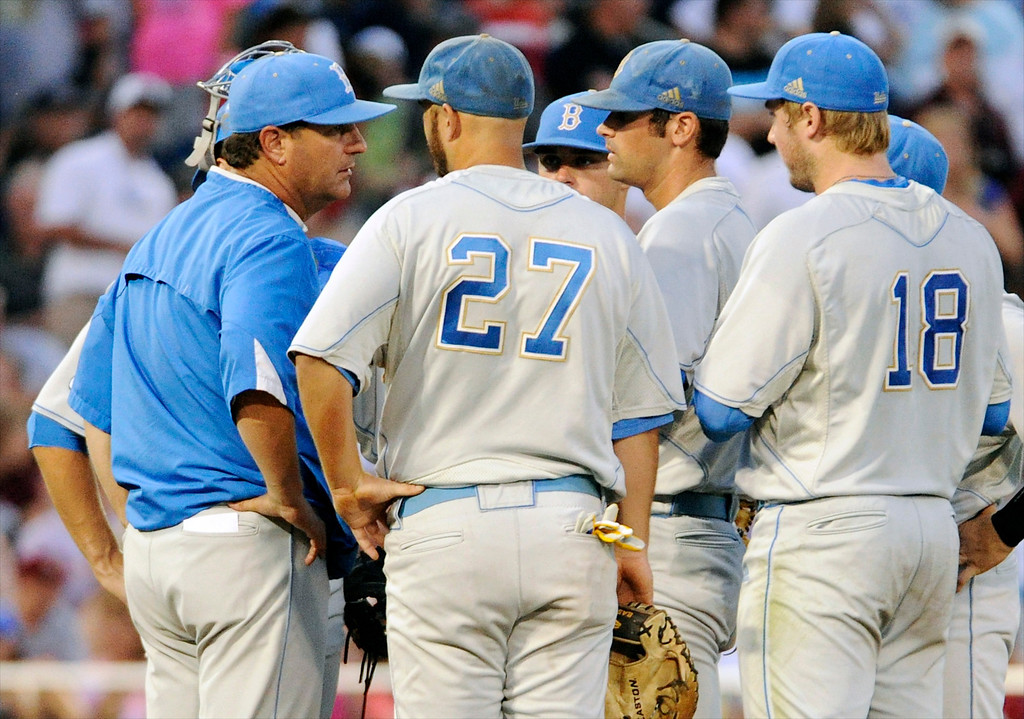 . UCLA coach John Savage, left, speaks to pitcher Adam Plutko, center right, on the mound in the fourth inning of Game 1 in their NCAA College World Series baseball finals against Mississippi State, Monday, June 24, 2013, in Omaha, Neb. (AP Photo/Francis Gardler)