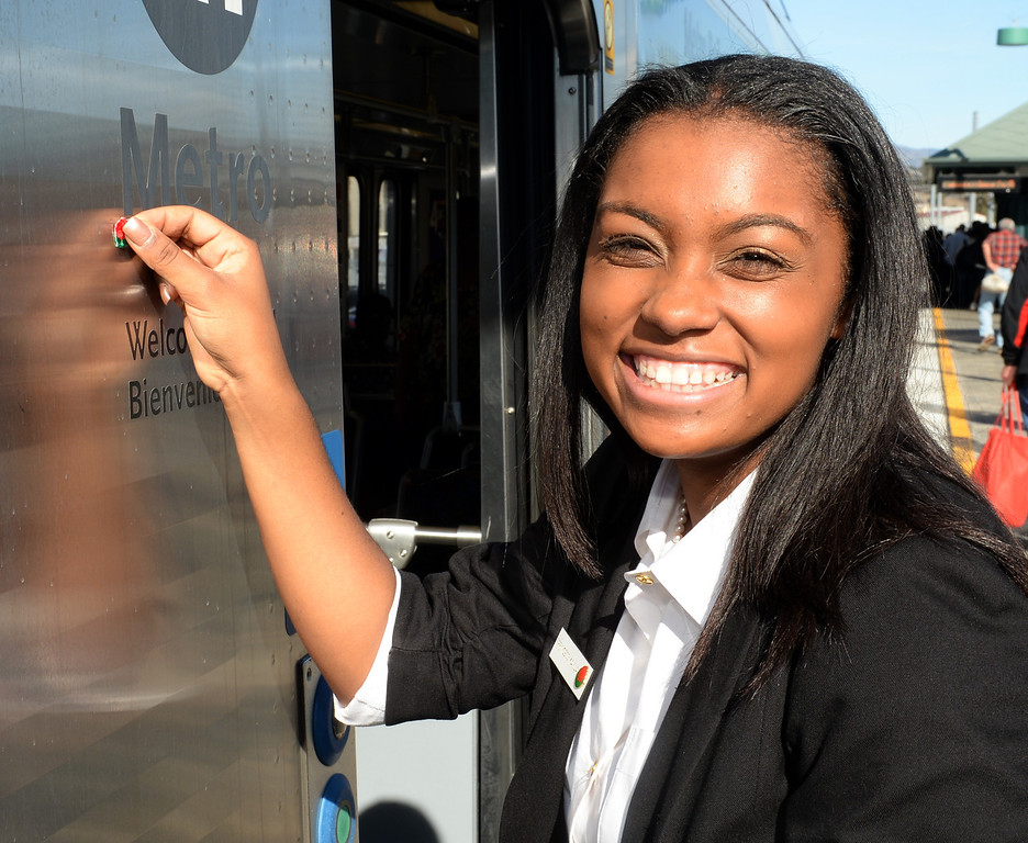 . The 2014 Tournament of Roses Princess Kayla Johnson-Granberry puts a Rose sticker on the Metro gold Line train at Union Station in Los Angeles on Friday December 27, 2013. The event is to commemorate the 10th official year of Metro Rail service to the Tournament of Roses parade events at Union Station. (Staff Photo by Keith Durflinger/Pasadena Star-News)