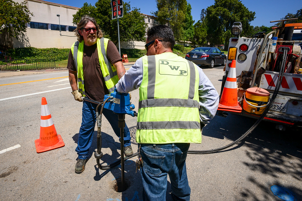 . DWP workers begin to slowly increase the water pressure with valves along Sunset blvd. where a water main broke last week releasing thousands of gallons of water and closing the busy street until early Monday morning.   ( Photo by David Crane/Los Angeles Daily News )