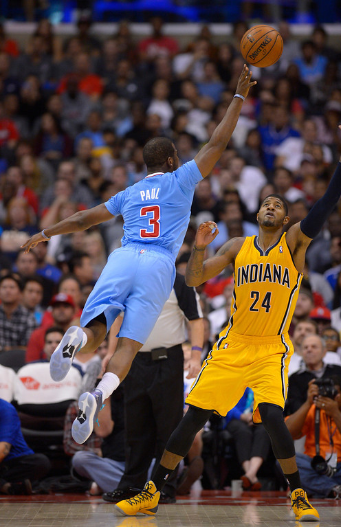 . Los Angeles Clippers guard Chris Paul, left, puts up a shot as Indiana Pacers forward Paul George defends during the first half of an NBA basketball game, Sunday, Dec. 1, 2013, in Los Angeles. (AP Photo/Mark J. Terrill)