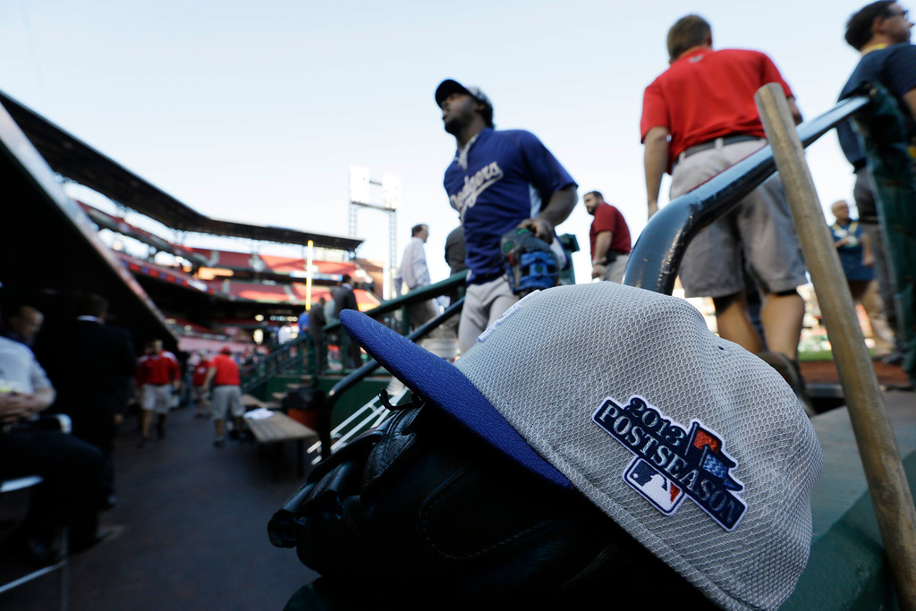 . A Hat rests in the Los Angeles Dodgers dugout before Game 1 of the National League baseball championship series against the St. Louis Cardinals, Friday, Oct. 11, 2013, in St. Louis. (AP Photo/David J. Phillip)