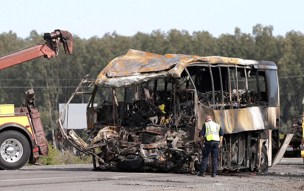 . A California Highway Patrol Officer looks over the burned out remains of a tour bus, Friday April 11, 2014, that collided with a FedEX truck on Interstate 5 Thursday in Orland, Calif.  At least ten people were killed and dozens injured in the fiery crash, Thursday, between the truck and a bus carrying high school students on a visit to a Northern California College.(AP Photo/Rich Pedroncelli)