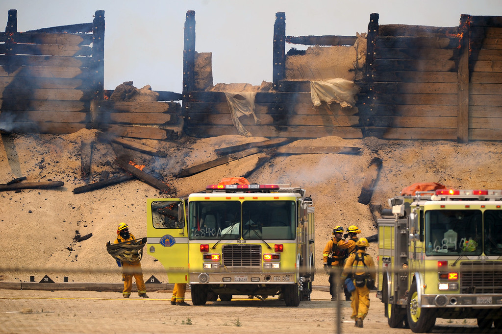 . Firefighters gather their hoses at a shooting range at Naval Base Ventura County that burnt from the Springs Fire, Friday, May 3, 2013. (Michael Owen Baker/Los Angeles Daily News)