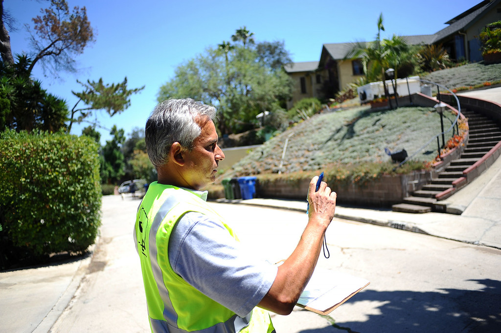 . Rick Silva of the DWP�s Water Conservation Response Unit stops to investigate a moist gutter while on patrol in the Sliver Lake area Wednesday July 17, 2014.  Silva is in charge of monitoring water violations in LADWP\'s service area of just under 500 square miles. (Andy Holzman/Los Angeles Daily News)