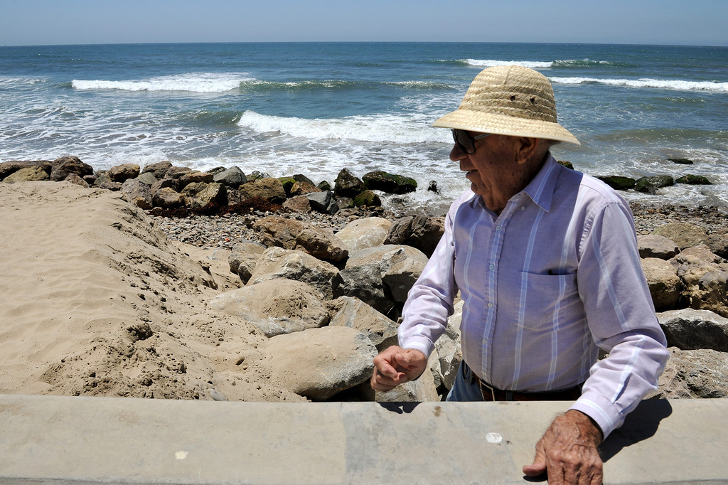 . Richard Dusckett holds onto the seawall as he walks along a washed-out section of Hueneme Beach in Port Hueneme, Monday, July 15, 2013. (Michael Owen Baker/L.A. Daily News)