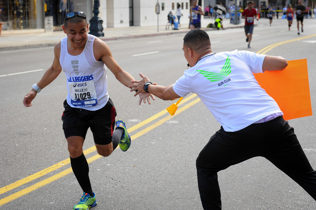 . Rodrigo Nadres, right, slaps hands with a runner in Beverly Hills during the Los Angeles Marathon, Sunday, March 9, 2014. (Photo by Michael Owen Baker/L.A. Daily News)