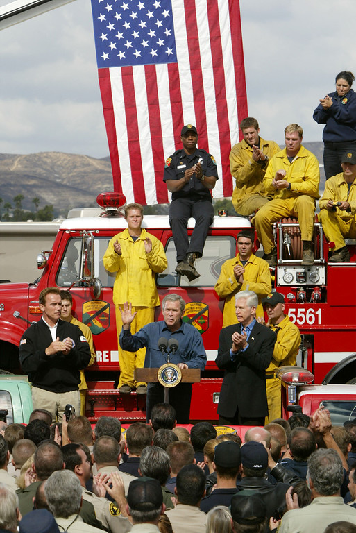 . EL CAJON, CA - NOVEMBER 4:  U.S. President George W. Bush, flanked by California Governor-elect Arnold Schwarzenegger (L) and California Gov. Gray Davis (R), speaks to firefighters who fought the Cedar Fire November 4, 2003 in El Cajon, California. San Diego County\'s 280,000-plus-acre Cedar Fire is the biggest in state history, killing at least 14 people and destroying more than 2,000 homes.  (Photo by David McNew/Getty Images