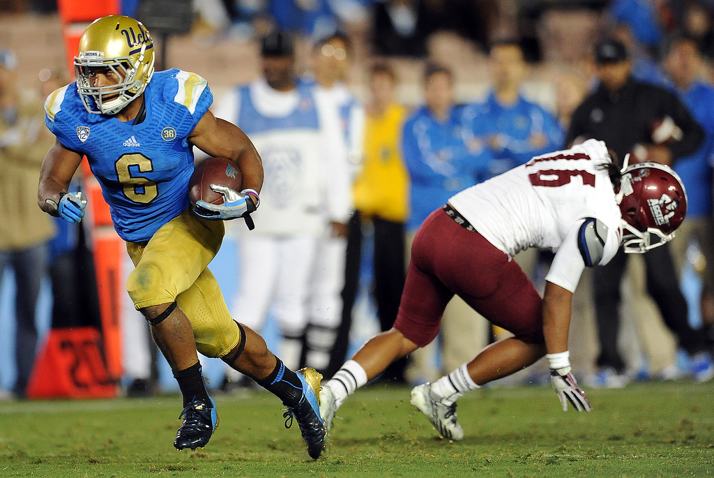 . UCLA running back Jordon James (6) runs for a first down past New Mexico State defensive back Kawe Johnson (16) during the second half of their college football game in the Rose Bowl in Pasadena, Calif., on Saturday, Sept. 21, 2013.   (Keith Birmingham Pasadena Star-News)
