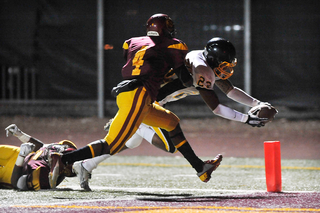 . LOS ANGELES - 10/04/2013 - (Mark Savage) San Pedro player Pete Palacios avoids a tackle by Fairfax player Jahson Brown and scores a touchdown in the second quarter. Fairfax High School plays San Pedro High School at Fairfax High School.