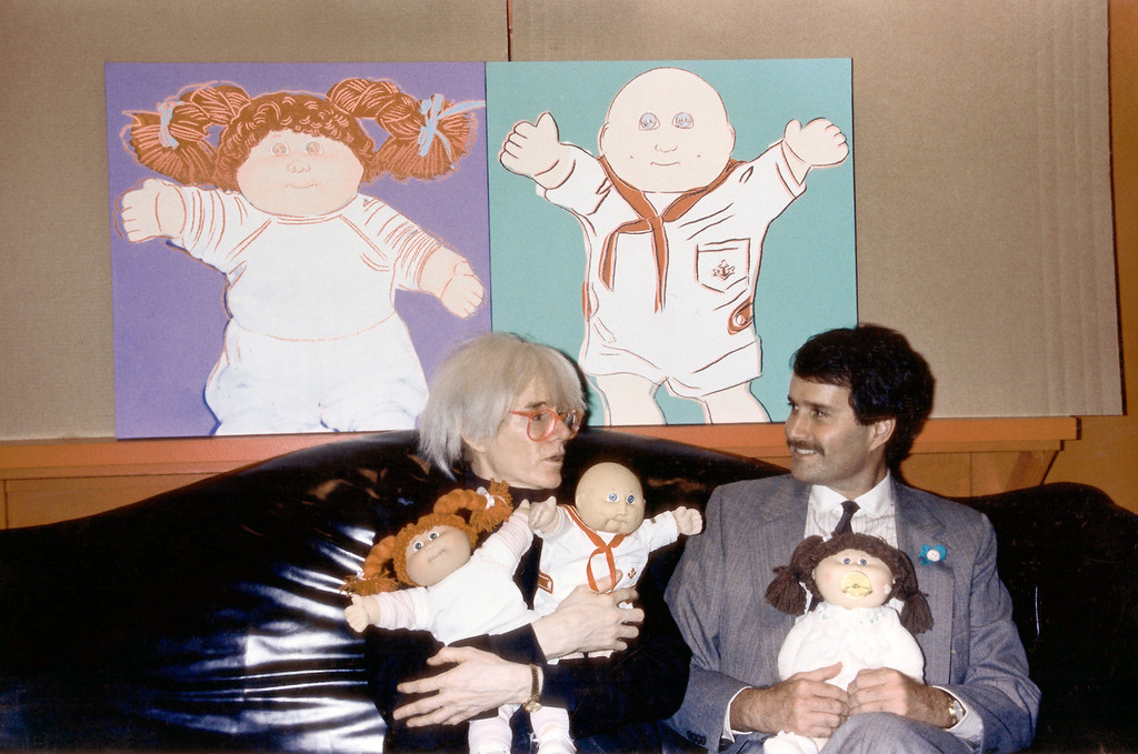 . Andy Warhol with unidentified man are shown seated in front of Warhol\'s Cabbage Patch Doll paintings and holding Cabbage Patch Dolls, circa 1985 in an undated photo. (AP Photo/Dave Pickoff)