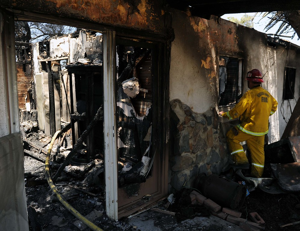 """. A vegetation fire in Jurupa Valley is 100 percent contained after destroying two homes and damaging two others.The Van Buren fire was kept to 12 acres nearly five hours after it started, said Scott Zisyak, a fire captain with Cal Fire.\""""We\'re releasing fire crews,\"""" Zisyak said about 1:30 p.m.More than 55 firefighters and sixteen fire engines responded when the fire began shortly before 8:30 a.m.No injuries were reported. In addition to the homes, five sheds and carports, 10 vehicles and one boat was destroyed by the fire.Van Buren Elementary School was evacuated and students were bussed to Mira Loma Middle School, Zisyak said. A Chevron station, located near Van Buren and Jurupa, was also evacuated.Some animals were removed from the neighborhood but residents were not asked to leave.As firefighters battled the flames, winds moved at 15 to 25 mph and stayed consistent, Zisyak said. The fire started on the center divider of Van Buren Boulevard and Jurupa Road, then jumped a road and got into nearby fields.Winds then pushed it the neighborhood. Officials believe a discarded hot object, most likely a cigarette, started the fire.LaFonzo Carter/ Staff Photographer"""