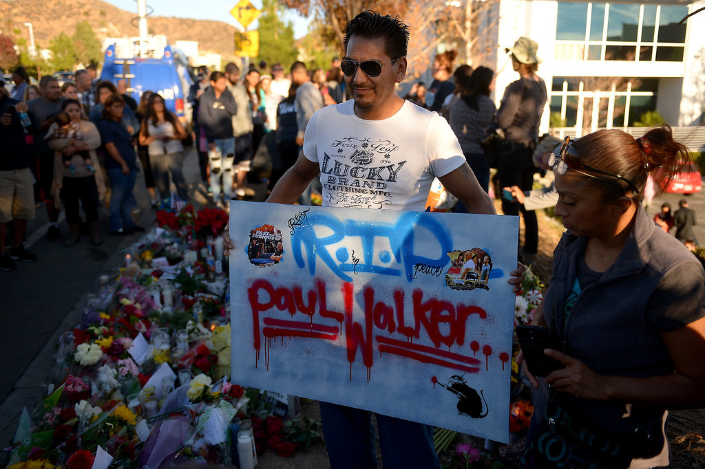 . Juan Luis Martinez has his picture taken with a sign at a memorial for Paul Walker and Roger Rodas, Sunday, December 1, 2013, at the scene of their fatal crash site on Hercules Street near Kelly Johnson Parkway in Valencia. (Photo by Michael Owen Baker/L.A. Daily News)