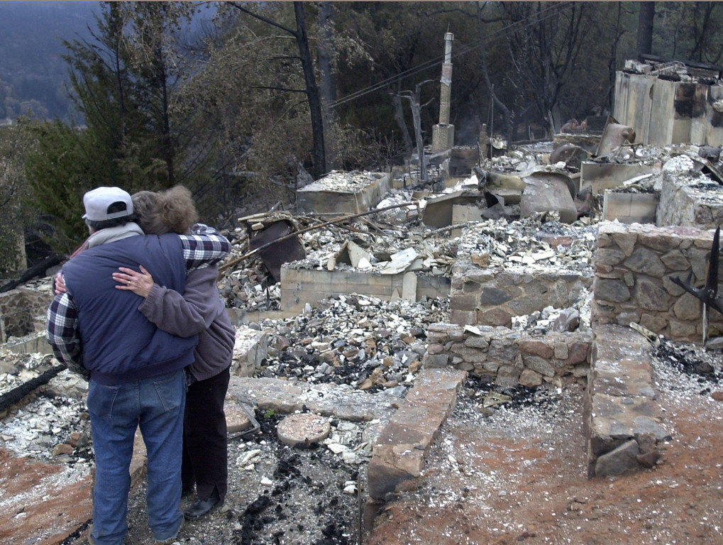 . Carol Brown, right, is hugged by a friend as she looks at the charred remains of her home in Cuyamaca, Calif. Nov. 1, 2003. Brown\'s home was one of 2,200 homes destroyed in the 275,000 acre Cedar fire east of San Diego. (AP Photo/Charlie Riedel)