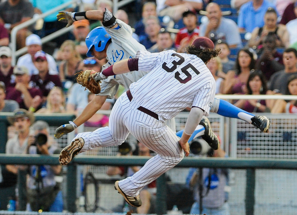 . Mississippi State first baseman Wes Rea (35) and UCLA\'s Brian Carroll, rear, are sent spinning after they collide at first base in the fourth inning of Game 1 of the NCAA College World Series best-of-three finals, Monday, June 24, 2013, in Omaha, Neb. Carroll safe on the play. (AP Photo/Eric Francis)