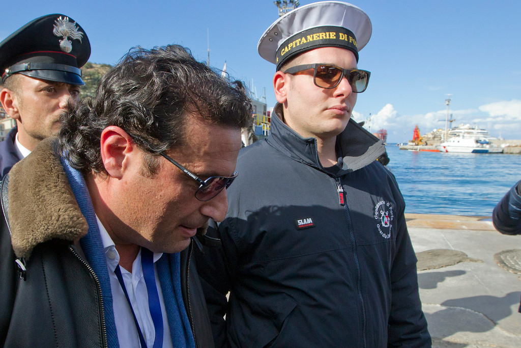 . Captain Francesco Schettino walks in Giglio port after boarding the wreck of the Costa Concordia cruise ship, just off the coast of the Giglio island, Thursday, Feb. 27, 2014. The captain of the Costa Concordia has been permitted to go aboard the shipwreck for the first time since it capsized two years ago as part of a new court-ordered search. Consumer groups and lawyers for Capt. Francesco Schettino asked the court in Grosseto to authorize the searches to determine if any factors beyond human error contributed to the disaster. After searching the bridge and elevators last month, experts will examine the emergency generators Thursday. (AP Photo/Andrew Medichini)