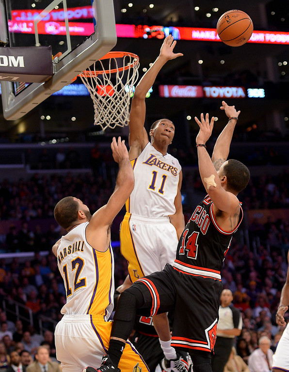 . The Los Angeles Lakers\' Wesley Johnson sails over the basket Chicago Bulls\' D.J. Augustin as Kendall Marshall assists in the NBA basketball game at Staples Center in Los Angeles, CA. on Sunday, Sunday, February 9, 2014. (Photo by Sean Hiller/ Daily Breeze).