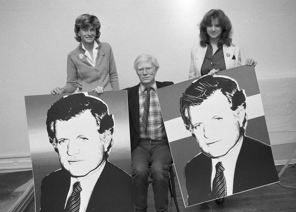 . Pop artist Andy Warhol holds up the red, white and blue poster of Sen. Edward M. Kennedy he created in order to raise $300,000 for the senator\'s presidential campaign through the sale of the poster, Feb. 4, 1980.  Warhol, seen in his Manhattan studio, is flanked by Jean Kennedy Smith, right, and Kerry Kennedy, daughter of the late Sen. Robert F. Kennedy. (AP Photo/Suzanne Vlamis)