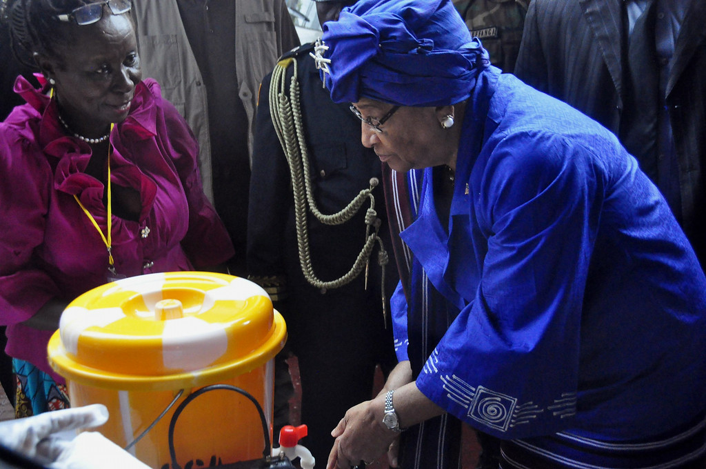 . In this photo taken on Saturday, July 26, 2014, Liberia President  Ellen Johnson Sirleaf, right, demonstrates to people how to wash their hands properly in order to prevent the spread of the Ebola virus, during  Independence Day celebrations in the city of Monrovia, Liberia. Scientists from Fort Detrick say the number of Ebola cases in West Africa is much larger than official estimates indicate. Researchers from the U.S. Army Medical Research Institute of Infectious Diseases, who have worked in Sierra Leone and Liberia, say the current outbreak reaches beyond the 1,200 confirmed, suspected or probable cases and over 600 deaths that the World Health Organization has identified in West Africa as of July 23. (AP Photo/Abbas Dulleh)