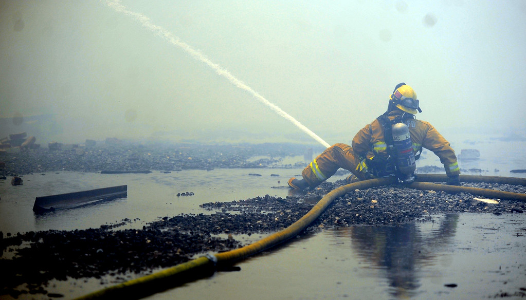 . Los Angeles County firefighter battles 3-alarm fire in heavy smoke at an abandoned warehouse near 9th Avenue and Clark Avenue on Tuesday, July 9, 2013 in City of Industry, Calif.  (Keith Birmingham/Pasadena Star-News)