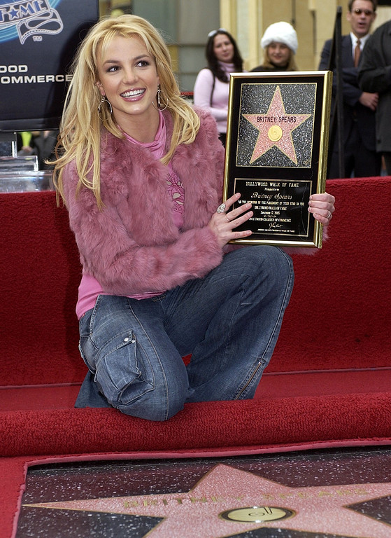 . Pop star Britney Spears poses for photographers with her new star on the Hollywood Walk of Fame, Monday, Nov. 17, 2003, in Los Angeles. Spears was honored with the 2,242nd star on the walk. (AP Photo/Nick Ut)