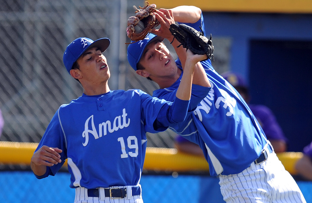. Bishop Amat starting pitcher Andrew Eppenbach catches a pop-up by Santiago\'s Deigo Lopez (not pictured) in front of Christian Moya (19) in the fourth inning of a CIF-SS Division 3 first round playoff baseball game against Santiago at Bishop Amat High School on Wednesday, May 15, 2013 in La Puente, Calif. Bishop Amat won 12-3.  (Keith Birmingham Pasadena Star-News)